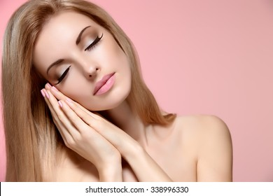 Beauty woman with closed eyes, sleep. Attractive nude blonde model girl on pink, perfect makeup, shiny straight hair. Face closeup, makeup, perfect skin. Rest concept