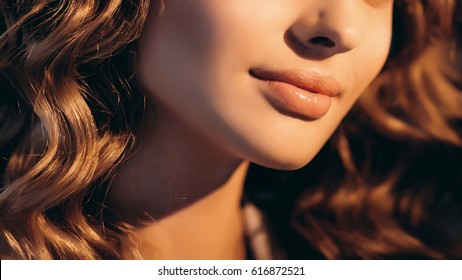 Beauty woman close-up detail portrait. Natural and perfect young woman plump lips. Lips enlarge with filler and results concept.