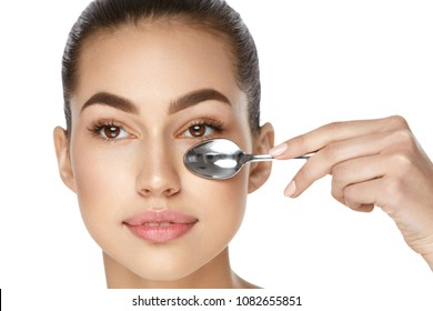 Beauty. Woman With Cold Spoon Near Eye