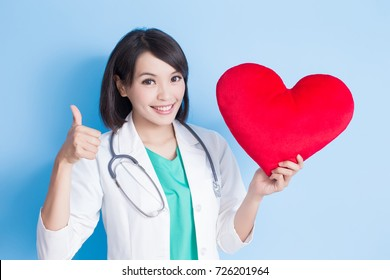 beauty woman dentist thumb up and take heart on the blue background