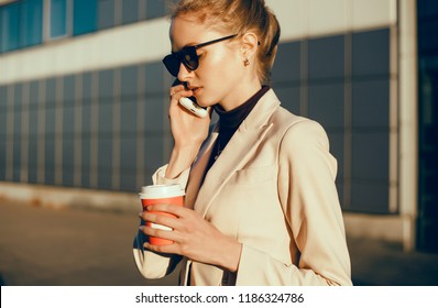 Beauty woman drinking coffee in the street, outdoor close up fashion portrait, office woman, sunset time, Young pretty woman using smartphone in cafe, drink coffee in cup, sweet breakfast, happy face,