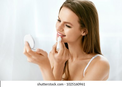 Beauty. Woman With Beauty Face Applying Lip Balm. Beautiful Female With Sexy Full Lips And Natural Makeup Applying Hygienic Lipstick Holding Mirror. Lips Skin Care Cosmetics Concept. High Resolution