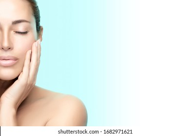 Beauty woman face. Beautiful brunette model girl with clean fresh skin, serene expression, hand to cheek, closed eyes. Half face over blue background. Cosmetology, Spa, Wellness and Skincare concept