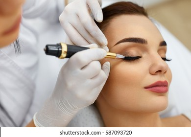 Beauty Woman Face. Beautiful Girl Receiving Permanent Make-Up From Beautician. Closeup Of Young Female Getting Eyelid Tattoo At Spa Salon. Makeup And Cosmetics. Cosmetology. High Resolution