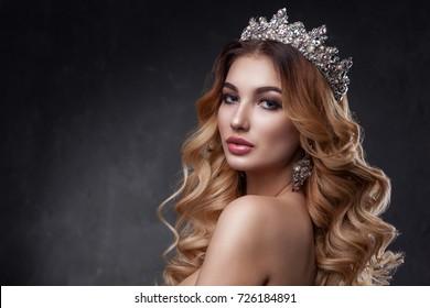 Beauty woman face with beautiful make-up colors. The image of the Queen. Dark hair, a crown on his head, clear skin, beautiful face, plump lips. Portrait shot in studio on a gray background.