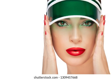 Beauty woman face. Beautiful model with healthy skin, plump red lips and nails holding hands to a cap with transparent green peak looking at camera. Fashion makeup and nail art. Beauty portrait isolat