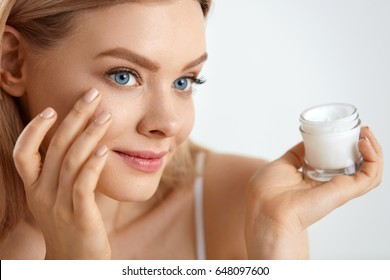 Beauty Woman Face. Closeup Of Beautiful Young Female Model With Fresh Skin Holding Cream Bottle In Hand. Portrait Of Sexy Girl Applying Cosmetic Product Under Eyes. Skincare Concept. High Resolution