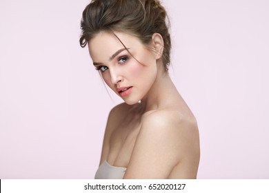 Beauty Woman Face. Closeup Of Beautiful Young Female Model With Fresh Natural Skin And Professional Facial Makeup On Pink Background. Portrait Of Sexy Girl With Glamour Hair Style. High Resolution