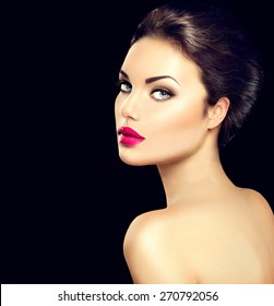 Beauty woman face closeup isolated on black background. Beautiful model girl makeup. Gorgeous lady with blue eyes and brown hair. Perfect skin. Professional make up. Red lips