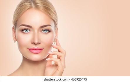 Beauty Woman face closeup Portrait. Beautiful Spa Girl Touching her Face and smiling. Perfect Fresh Skin. Pure Beauty Model Female looking at camera. Youth and Skin Care Concept. Beige background