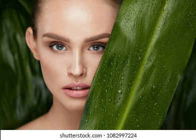 Beauty Woman Face With Healthy Skin And Green Plant