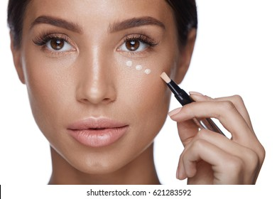 Beauty Woman Face Makeup. Closeup Of Beautiful Young Female Applying Corrector On Skin Under Eyes. Portrait Of Attractive Sexy Girl With Soft Skin Applying Concealer. Cosmetics. High Resolution