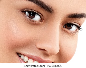 Beauty Woman face Portrait. Beautiful model Girl with Perfect Fresh Clean Skin brunette hair Youth and Skin and healthy teeth smile Care Concept. Isolated on a white background. Studio shot.