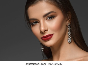 Beauty Woman face Portrait. Beautiful Spa model Girl with Perfect Fresh Clean Skin. Brunette female red lipstick smiling on gray background.