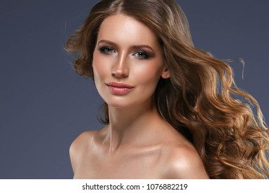 Beauty Woman face Portrait. Beautiful Spa model Girl with Perfect Fresh Clean Skin.  female looking at camera and smiling on gray background. Beautiful hairstyle Youth and Skin Care Concept.