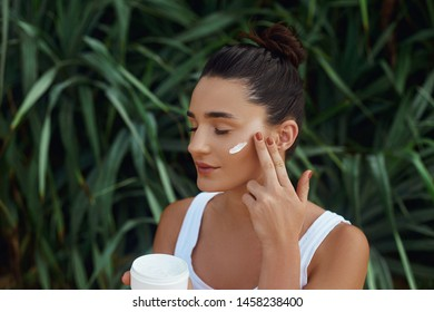 Beauty Woman face Portrait. Beautiful Spa model Girl with Perfect Fresh Clean Skin. Holdinging and apply moisturizing cream. Skin care.  Facial treatment. Cosmetology, beauty in tropical nature