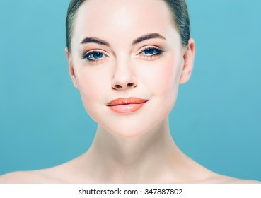 Beauty Woman face Portrait. Beautiful Spa model Girl with Perfect Fresh Clean Skin. Brunette female looking at camera and smiling. Youth and Skin Care Concept.Blue background gray