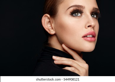 Beauty Woman Face. Portrait Of Beautiful Sexy Young Female With Perfect Facial Makeup, Soft Fresh Healthy Skin And Thick Long Black Eyelashes. Glamorous Girl On Black Background. High Resolution