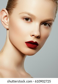 Beauty woman Face. Portrait of beautiful sexy young female with perfect matte facial makeup. Soft healthy skin. Glamorous girl on gray background. Red lips
