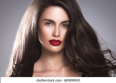 Beauty Woman face Portrait. Beautiful Spa model Girl with Perfect Fresh Clean Skin. Brunette female looking at camera and smiling on gray background. Beautiful hairstyle Youth and Skin Care Concept