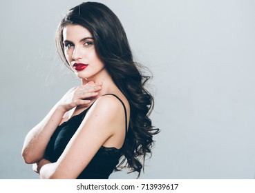 Beauty Woman face Portrait. Beautiful Spa model Girl with Perfect Fresh Clean Skin model female looking at camera and smiling on gray background. Beautiful hairstyle Youth and Skin Care Concept