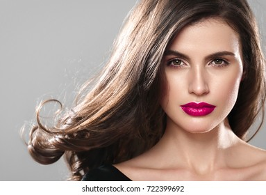 Beauty Woman face Portrait. Beautiful Spa model Girl with Perfect Fresh Clean Skin. Brunette female looking at camera and smiling on gray background with fly hair.