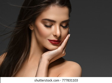 Beauty Woman face Portrait. Beautiful Spa model Girl with Perfect Fresh Clean Skin. Brunette female red lipstick smiling on gray background. Beautiful hairstyle Youth and Skin Care Concep