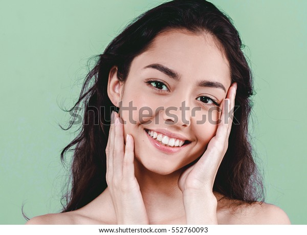 Beauty Woman face Portrait. Beautiful Spa model Girl with Perfect Fresh Clean Skin. Brunette female looking at camera and smiling. Youth and Skin Care Concept over Green nature fresh background.