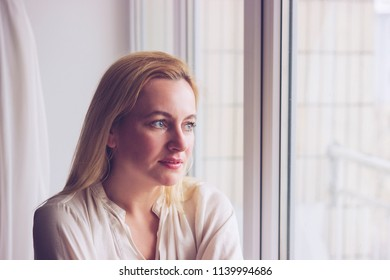 Beauty Woman face Portrait.  Blond female looking through the window and smiling. Toned portrait. Soft focused