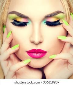 Beauty Woman face Portrait with Vivid Makeup and colorful Nail polish. Colourful nails. Fashion Girl close up. Bright Colors. Manicure Make up. Smoky eyes, long eyelashes. Rainbow Colors