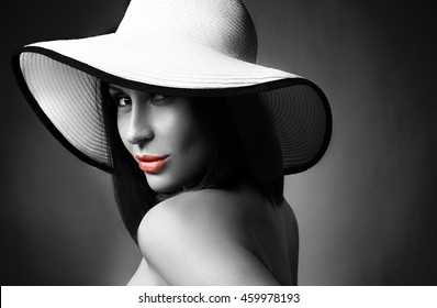 Beauty Woman face Portrait in a white hat. Beautiful model Girl with Perfect Clean Skin. Female looking at camera. Youth and Skin Care Concept. Isolated on a dark background