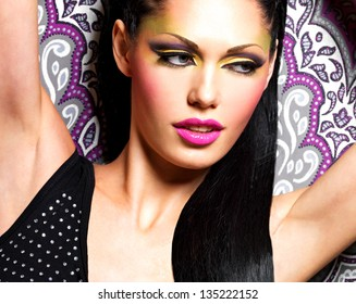 Beauty  woman with fashion makeup on  face poses at studio
