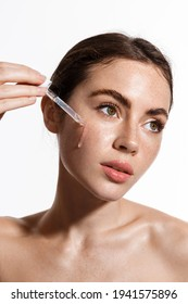 Beauty woman with freckles, naked shoulders and nude face, apply serum vitamin c, argan oil tea tree ingredients in pippette dropper under eye, treating skin for nourishing and moisturizing effect.