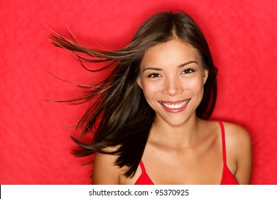 beauty woman happy. Beautiful fresh multiracial girl smiling fresh and natural on red background. Multicultural Caucasian / Chinese Asian young woman model.