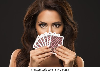 Beauty woman is hiding under playing cards, only eyes and poker face