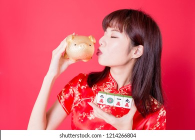 beauty woman hold Mahjong kiss golden pig bank - rich and ten thousand in chinese word