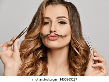 Beauty woman hold makeup professional tools for manicure cuticle forceps scissors tweezers make funny mustache with eyelashes on face