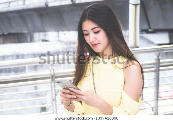 Beauty woman holding many shopping bags and smartphone for shopping online with walking on street in city in fashion boutique.