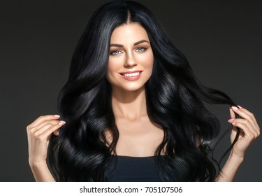 Beauty Woman long black hair. Beautiful Spa model Girl with Perfect Fresh Clean Skin. Brunette woman smiling on black background. Beautiful hairstyle