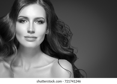 Beauty Woman long black hair. Beautiful Spa model Girl with Perfect Fresh Clean Skin. Brunette woman smiling on black background. Beautiful hairstyle black and white