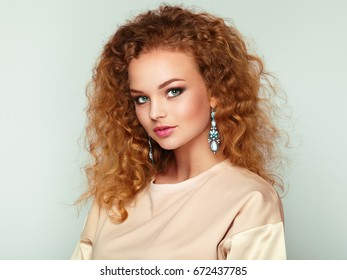 Beauty woman with long and shiny curly hair. Perfect make-up. Beauty style model with jewelry. Fashion photo
