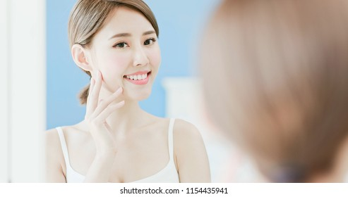 beauty woman look mirrior happily and touch her face