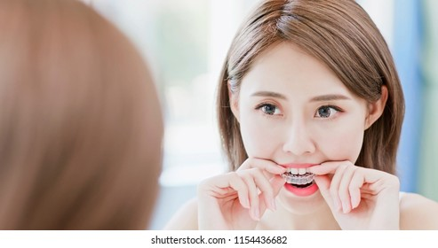 beauty woman look mirror smile happily and take invisible brace