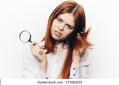 Beauty woman looking through a magnifying glass to split hairs..