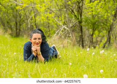 Beauty woman lying down on grass in nature