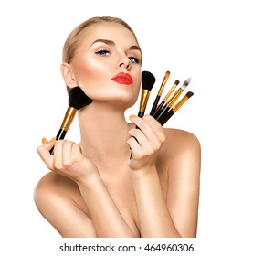 Beauty Woman with Makeup Brushes. Natural Make-up for Blonde Model Girl with Blue Eyes. Beautiful Face. Perfect Skin. Applying Holiday Makeup, orange color lipstick and manicure over white background