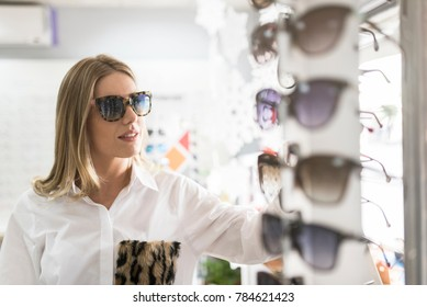 Beauty woman in optical store with sunglasses looking at display