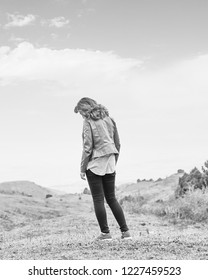 Beauty woman outdoors enjoying nature mountains. Pretty young woman in field at bad weather. Black and white tone.