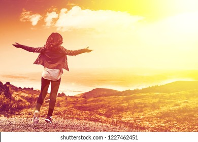 Beauty woman outdoors enjoying nature. Pretty young woman in field at sunset in the mountains