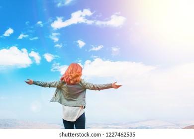 Beauty woman outdoors enjoying nature. Beautiful Teenage Model girl on summer Field, Sun Light. Free Happy Woman. Toned in warm colors